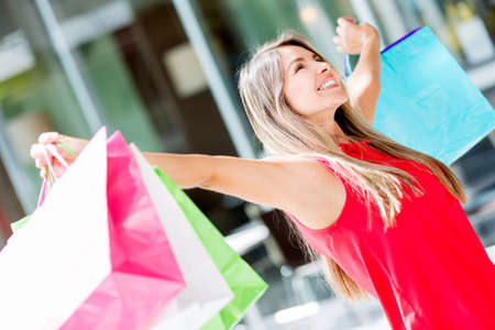 Excited shopping woman with arms open holding bags Stock Photo - 17482281