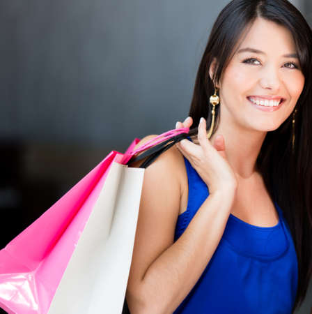 Beautiful shopping woman holding bags and smiling Stock Photo - 17482424