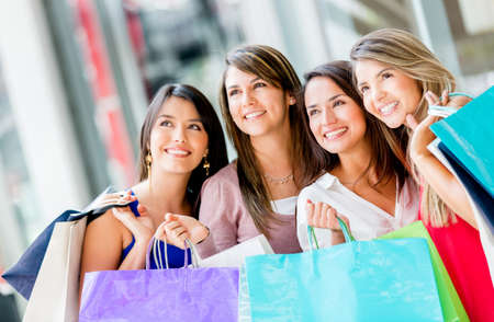 Group of beautiful shopping women holding bags photo