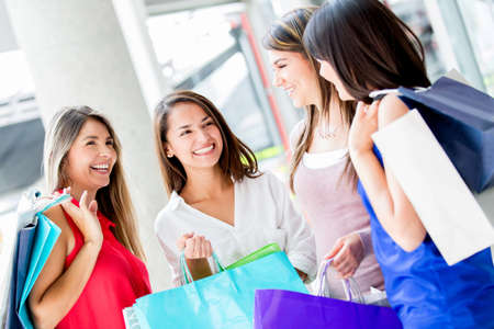 Group of female shopping friends talking at the mall photo