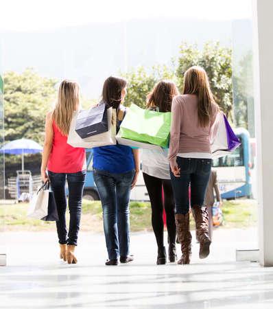 compras compulsivas: Grupo de mujeres que salen del centro comercial