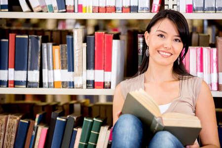 biblioteca: Mujer en la biblioteca leyendo un libro