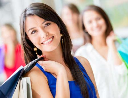 chicas comprando: Compras mujer feliz con un grupo de amigos en el fondo Foto de archivo