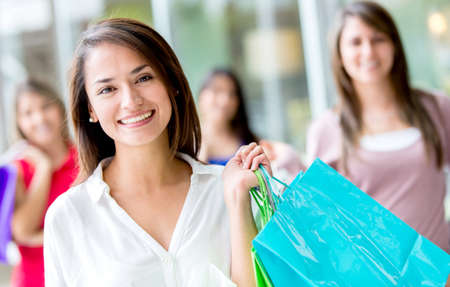Beautiful female shopper holding bags and smiling Stock Photo - 17425378