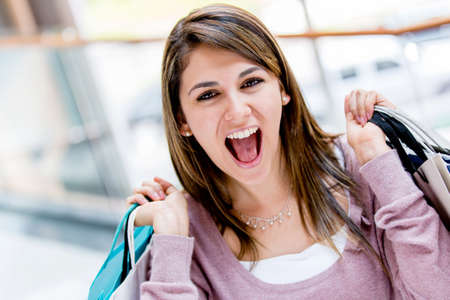 Happy shopping woman looking very excited and screaming Stock Photo - 17425382