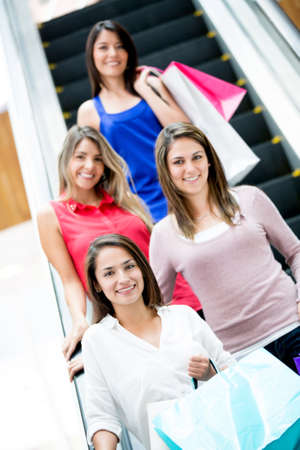 Happy women at the shopping center on the escalators photo