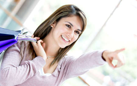 Casual shopping woman pointing away with her finger Stock Photo - 17425386