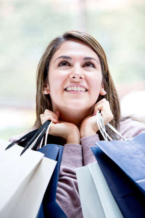Thoughtful female shopper holding shopping bags photo