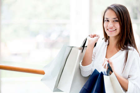 Shopping woman holding bags and smiling at the mall Stock Photo - 17405957