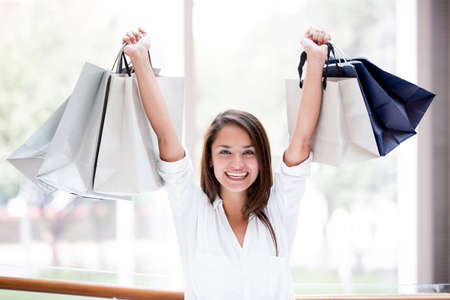 Excited shopping woman with arms up holding bags Stock Photo - 17425394