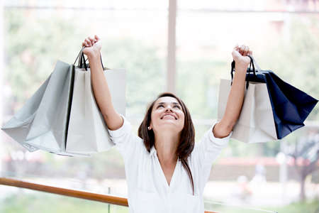 Happy shopping woman with arms up holding bags Stock Photo - 17425384