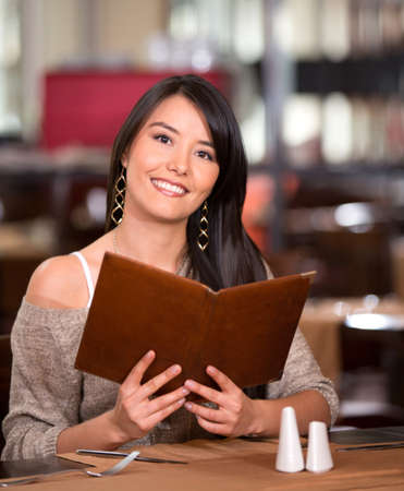 Woman in a restaurant looking at the menu Stock Photo - 17425380