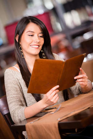 Beautiful woman looking at the menu in a restaurant Stock Photo - 17425392