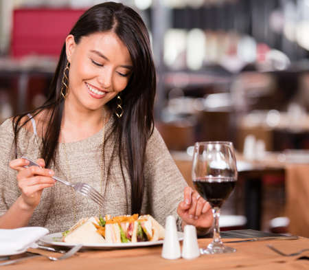 Woman eating at a restaurant looking very happy Stock Photo - 17425391