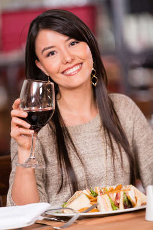 Beautiful woman having dinner at a restaurant and drinking wine Stock Photo - 17425379