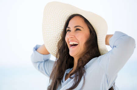 Happy woman at the beach wearing a summer hat Stock Photo - 17504670