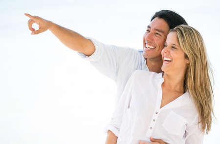 far away look: Couple outdoors pointing far away and looking happy Stock Photo