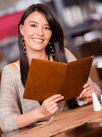 Woman at a restaurant holding the menu and smiling Stock Photo - 17482217