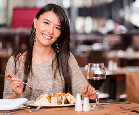 Woman at a restaurant having lunch and looking happy photo