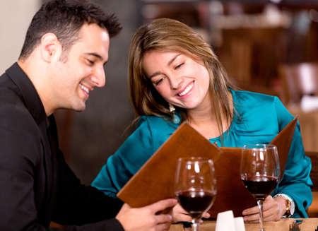 dattes: Couple romantique dans un restaurant regardant le menu