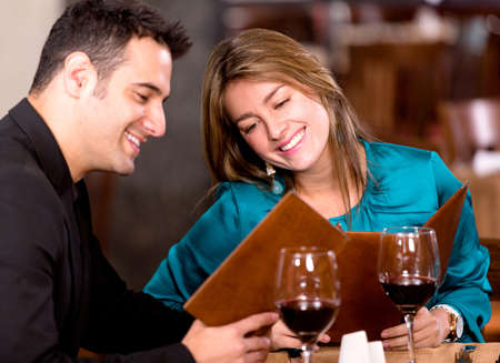 date: Romantic couple at a restaurant looking at the menu Stock Photo