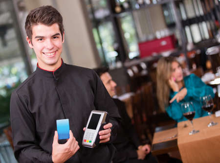 Waiter holding a dataphone at the restaurant photo