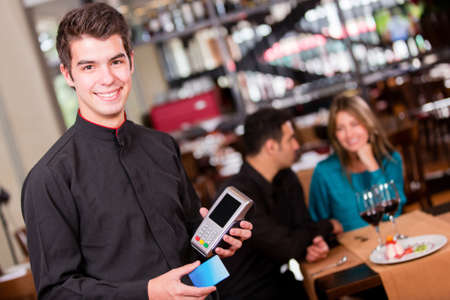 Waiter taking a payment by credit card at the restaurant photo