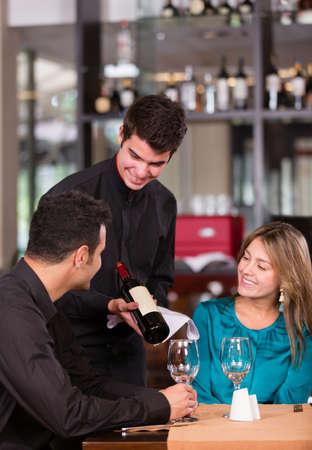 meseros: Pareja tratando un poco de vino tinto en un restaurante Foto de archivo