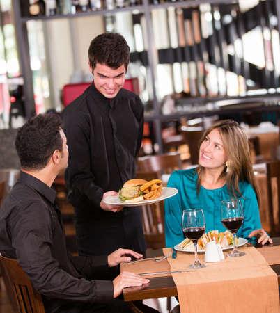 pareja comiendo: Pareja feliz comiendo en un restaurante y sonriente