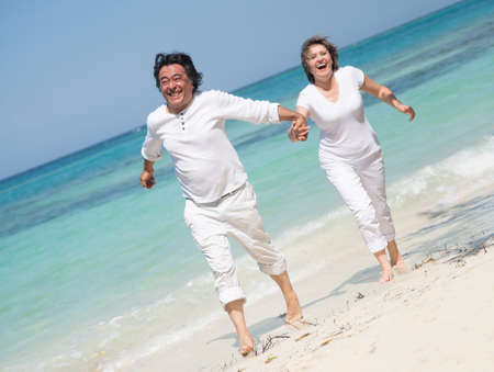 Beautiful couple on holidays running at the beach Stock Photo - 17505217