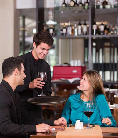 camarero: Pares en una cena rom�ntica en el restaurante Foto de archivo