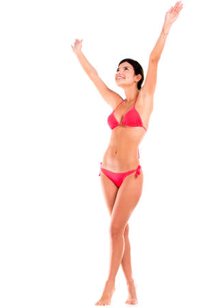 Happy woman in bikini with arms up - isolated over white photo