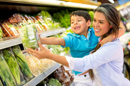 groceries: Woman at the supermarket with her son buying groceries