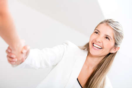 Business woman giving a handshake and looking happy Stock Photo - 17679835