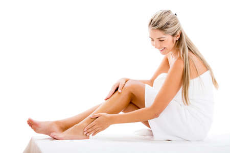 Beautiful woman applying cream on her legs - isolated over white Stock Photo - 17679932