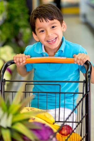 ni�os de compras: Ni�o jugando con un carrito de compras en el supermercado Foto de archivo
