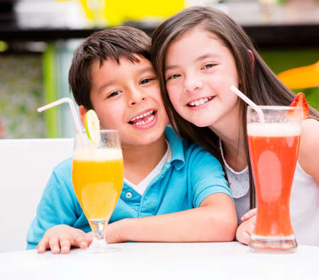 Happy kids at the diner drinking juice photo