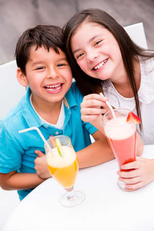 Kids drinking juice at a restaurant and smiling Stock Photo - 17680003