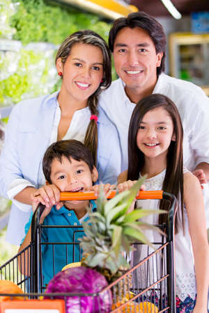 latin girls: Happy family at the supermarket with a shopping cart Stock Photo