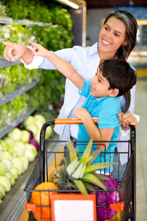 Woman grocery shopping with her kid at the supermarket photo