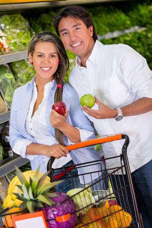 Happy couple grocery shopping at the supermarket photo