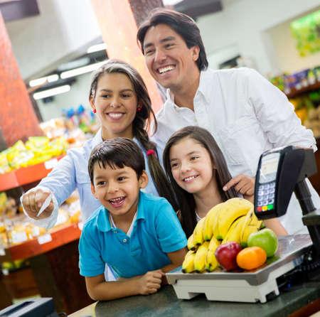 pagando: Familia feliz que pagar por provisiones en el supermercado