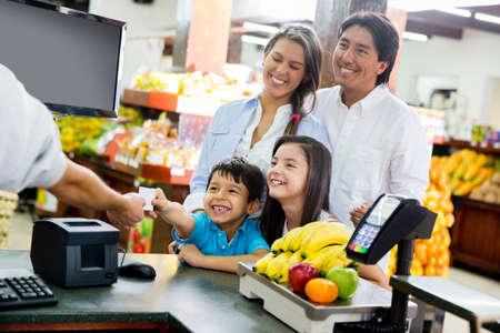 pagando: Familia mirando hacia fuera para las finanzas del hogar en el supermercado