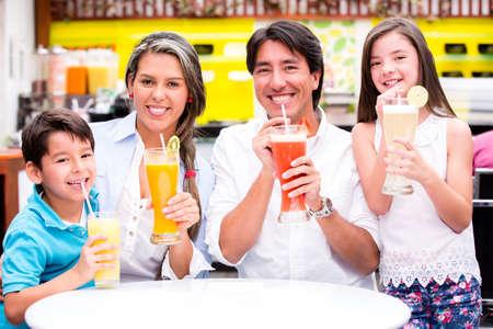 tomando jugo: Familia feliz en una cafeter�a bebiendo zumos naturales