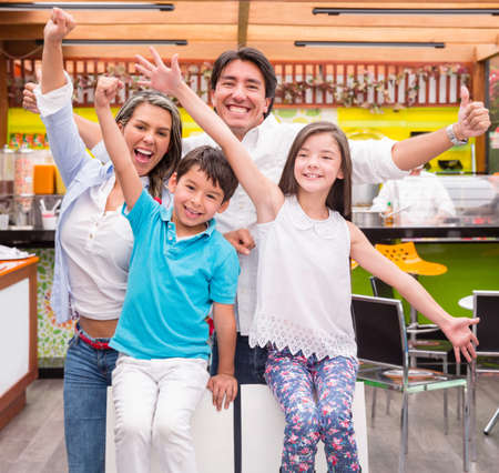 Excited  family at a cafeteria with arms up photo