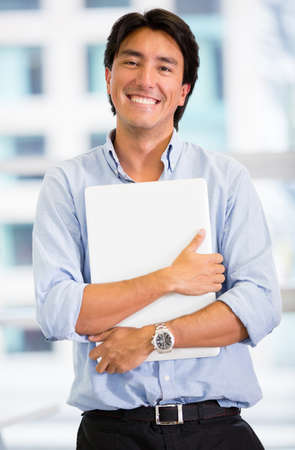 Businessman holding a laptop computer at the office Stock Photo - 17749750