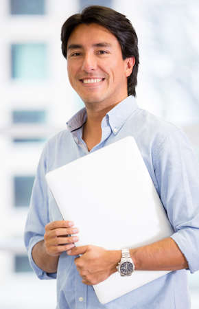 Executive man holding a laptop at the office Stock Photo - 17749744