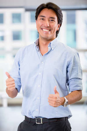 Happy businessman with thumbs up at the office Stock Photo - 17749746