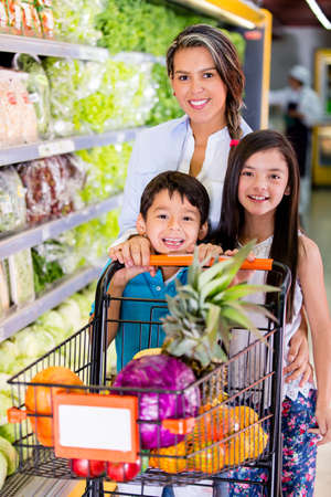 Mother shopping at the supermarket with her kids photo