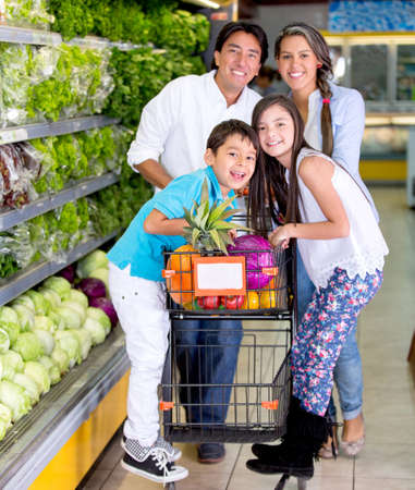 woman shopping cart: Happy family with a shopping trolley at the supermarket